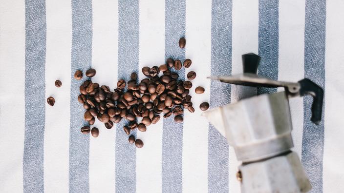 Espressobohnen und Espressokocher auf einem gestreiften Tischtuch