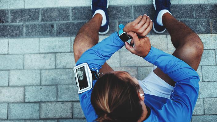 Sportler macht eine Pause und checkt seine Smartwatch