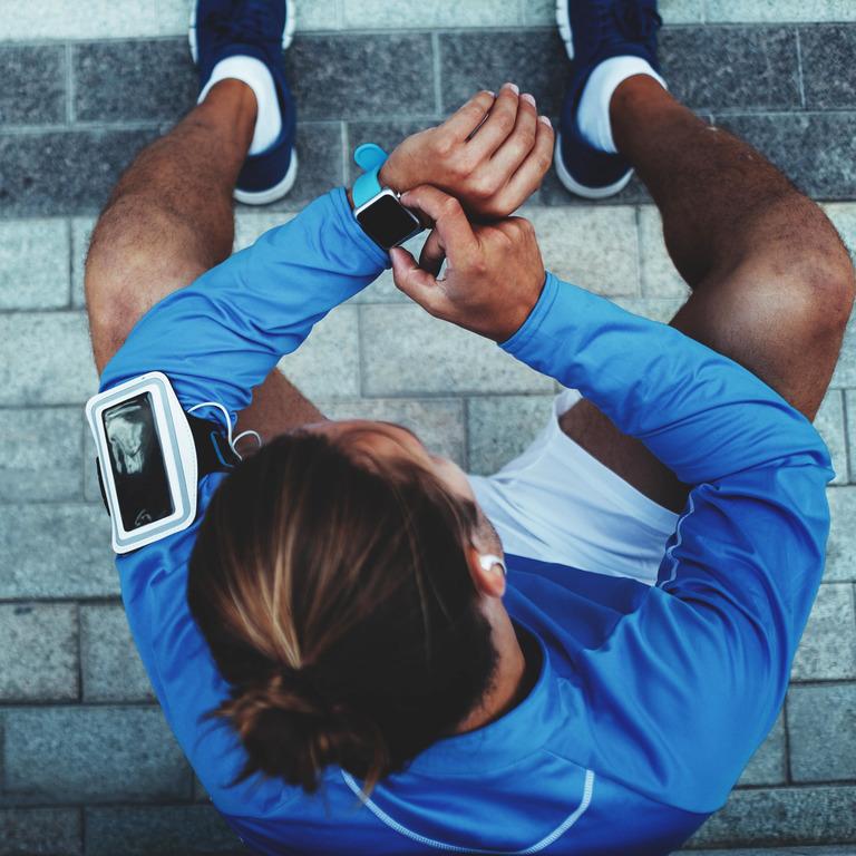Mann mit Fitness-Tracker und Sportsachen sitzt auf Treppe und macht Pause.