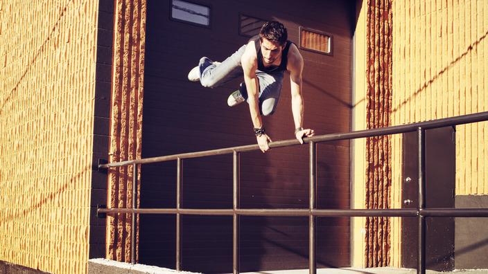 Junger Mann springt über ein Treppengeländer