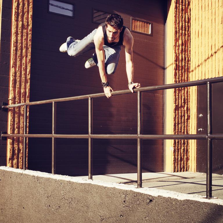 Junger Mann springt über Treppengeländer