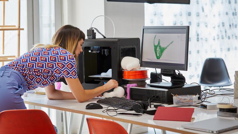 Junge Frau an Schreibtisch voller technischer Geräte