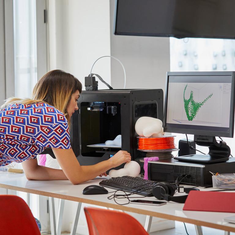Frau baut am Schreibtisch ein Modell nach, dass sie am Computer entworfen hat.