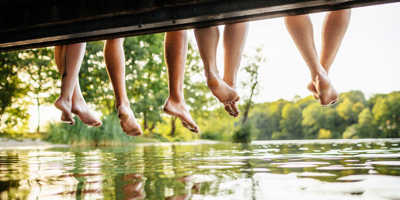Vier Menschen sitzen an Steg und lassen ihre Beine über dem See baumeln.
