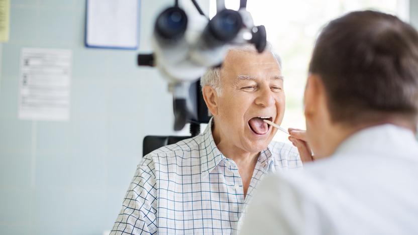 Älterer Herr sitzt mit geöffnetem Mund vor einem Arzt, der mit einem Stäbchen seine Zunge herunterdrückt