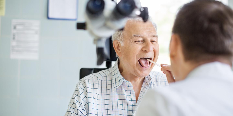 Arzt untersucht grauhaarigen Mann mit Stäbchen im Mund.
