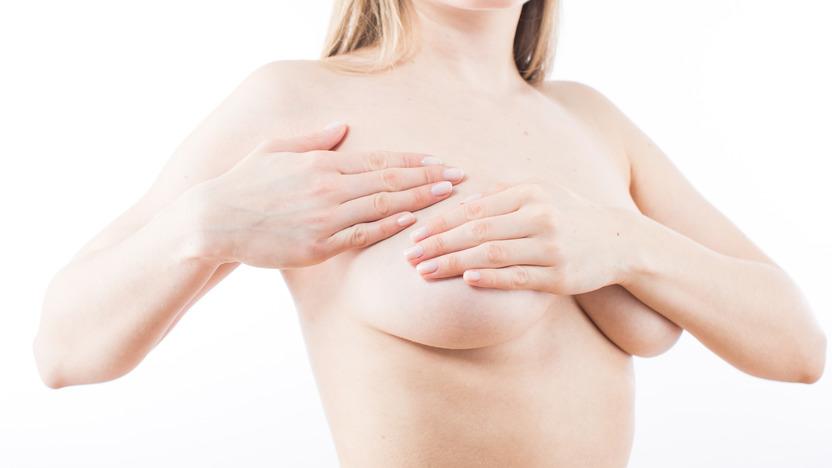 Nackte Frau tastet ihre Brust mit den Fingern ab