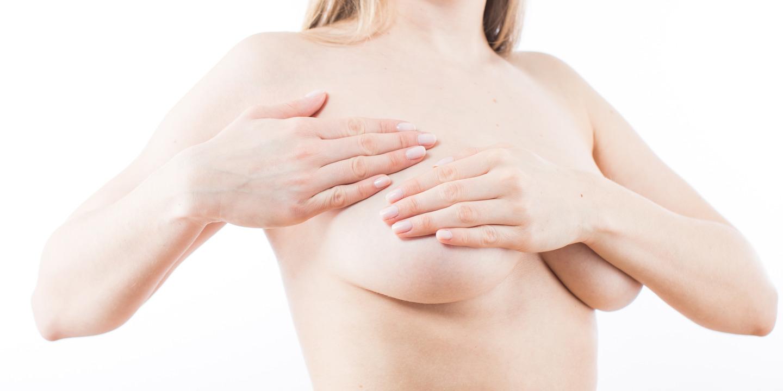 Oberkörperfreie Frau tastet ihre rechte Brust ab.