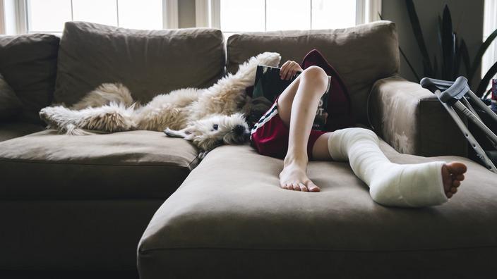 Teenager liegt mit eingegipstem Bein auf einer Couch