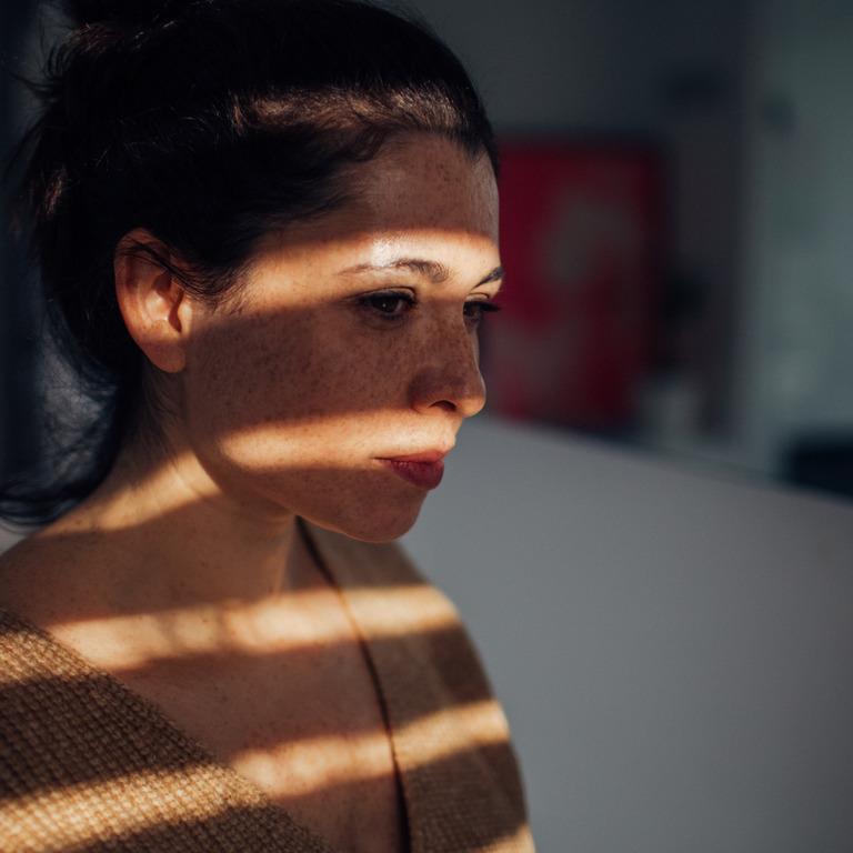 junge Frau steht am Fenster und schaut traurig nach draußen