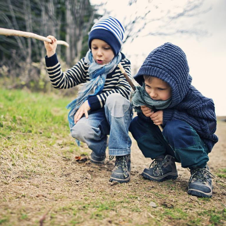 zwei Jungen hocken auf dem Boden eines Feldweges und suchen etwas