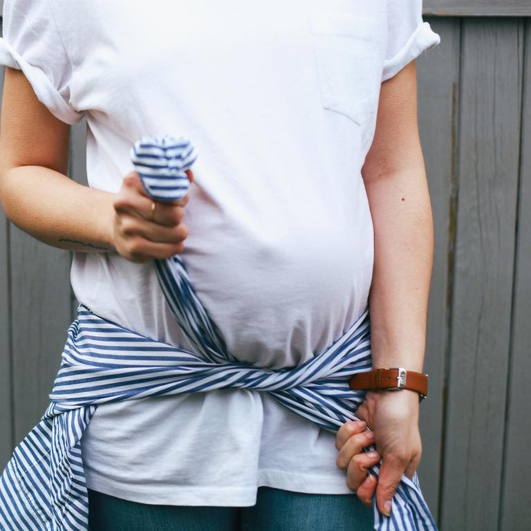 Schwangere knotet sich ein blau-weiß-gestreiftes Hemd unter ihrem Bauch um die Hüften