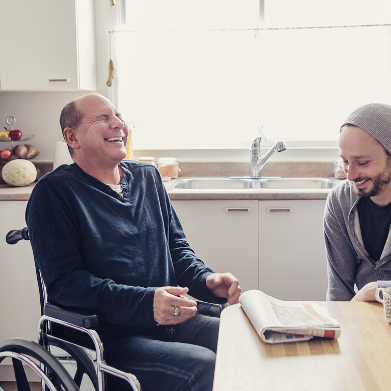Älterer Mann sitzt lachend im Rollstuhl in der Küche, daneben sitzt ein junger Mann am Tisch