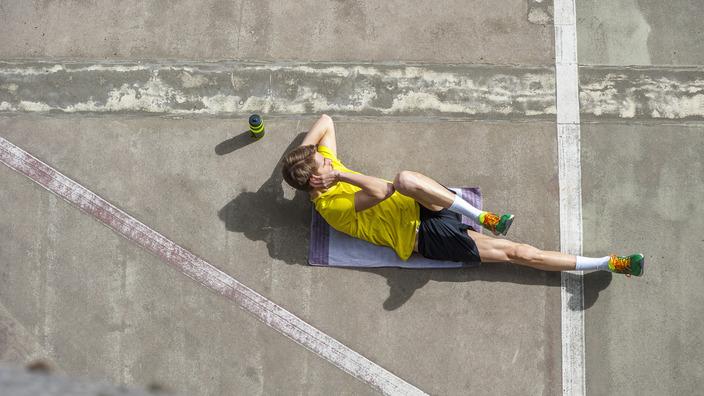 Mann in Sportkleidung liegt auf einem Handtuch und macht Übungen für die Bauchmuskulatur