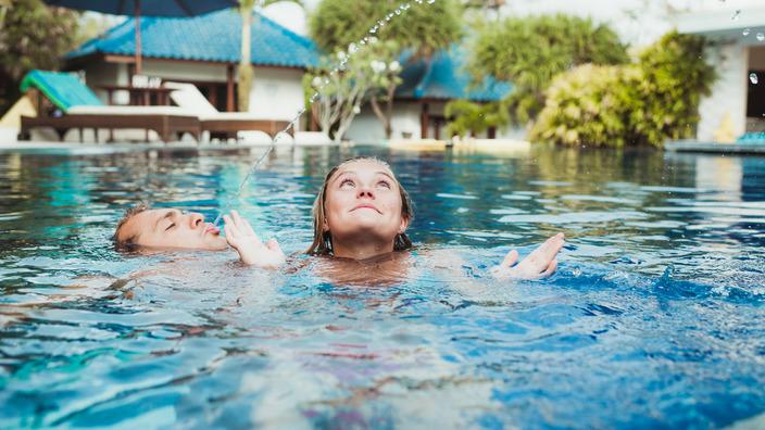 Junges Pärchen schwimmt im Pool.