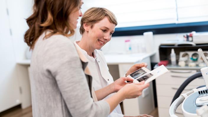 Frauenärztin und schwangere Patientin betrachten gemeinsam ein Ultraschallbild