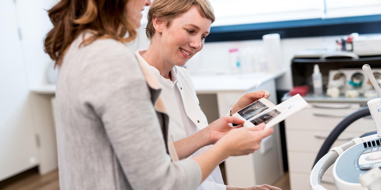 Schwangere Frau und ihre Ärztin betrachten ein Ultraschallbild.