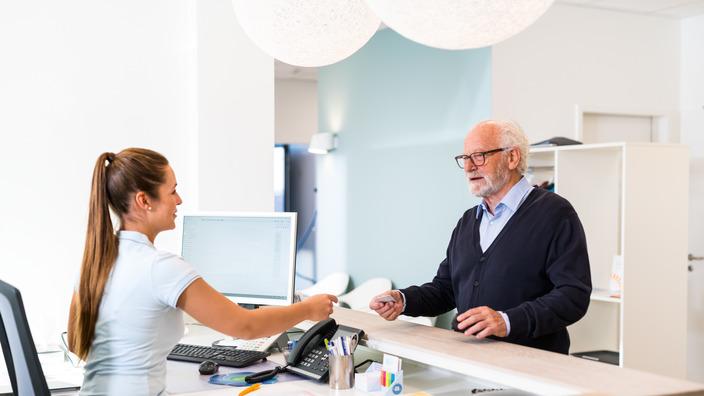 Sprechstundenhilfe reicht einem ältereren Patienten seine Versichertenkarte