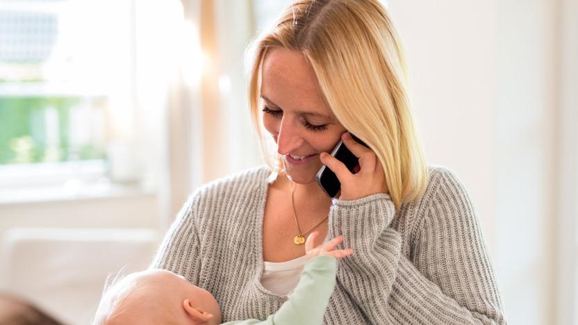 Mutter trägt Baby auf dem Arm und telefoniert