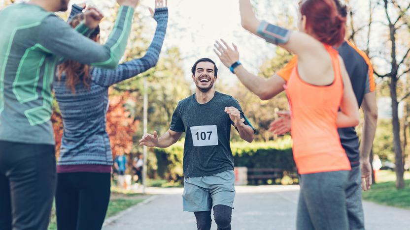 Läufer mit Startnummer 107 rennt auf eine kleine Gruppe von jubelnden Menschen zu.