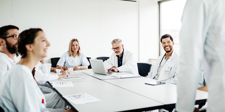 Gruppe von Ärzten sitzt an einem Besprechungstisch