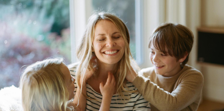Junge Mutter sitzt lachend mit Kindern auf dem Sofa