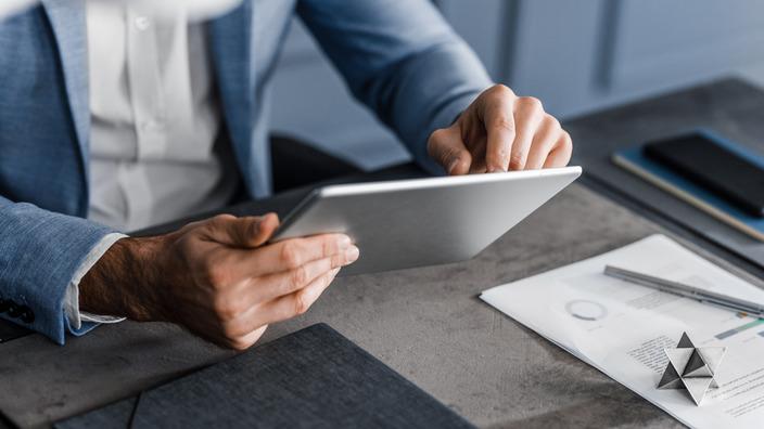 Arbeitnehmer berechnet etwas auf dem Tablet