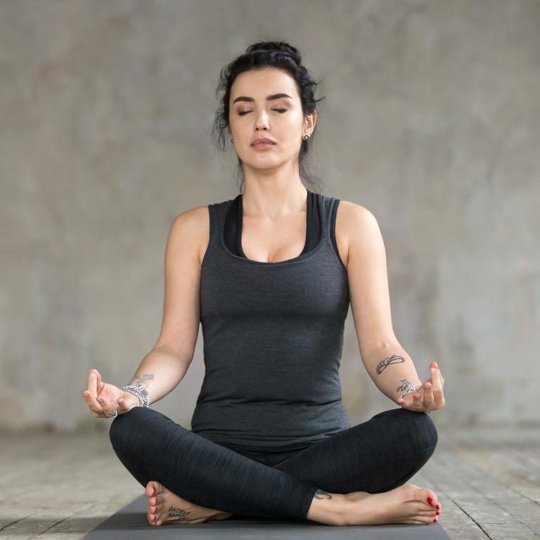 Frau sitzt in typischer Yoga-Haltung und praktiziert die Blasebalg-Atmung