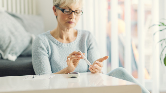 Frau mittleren Alters prüft ihren Blutzuckerspiegel