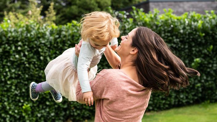 Mutter und kleine Tochter tollen durch den Garten
