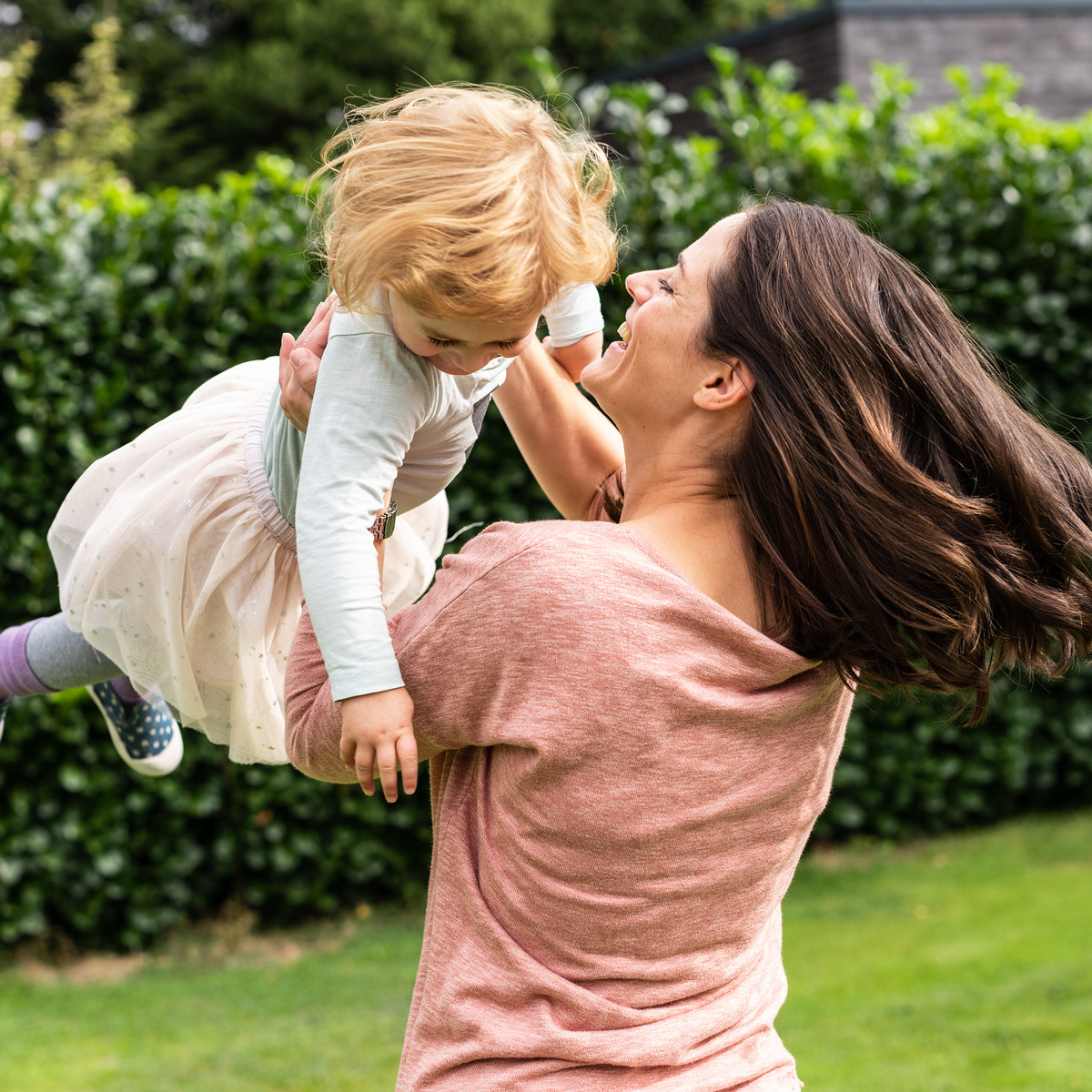 Mutter und Tochter spielen im Garten