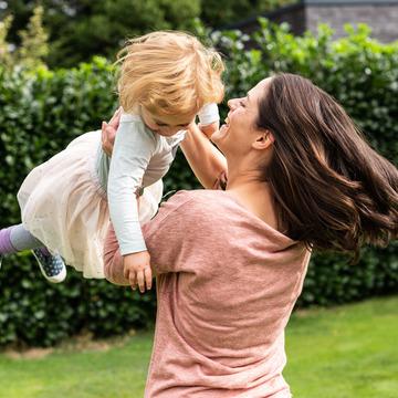 Muter wirbelt ihre Tochter durch die Luft