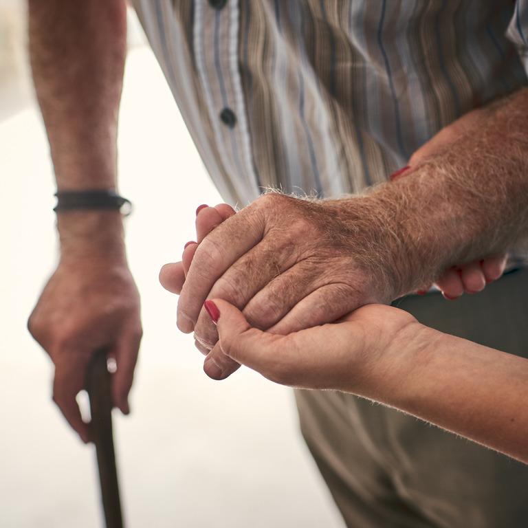 Pflegekraft stützt den Arm eines älteren Mannes mit Gehstock
