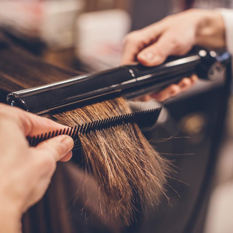 Friseurin führt Glätteisen und Kamm durch das Haar ihrer Kundin