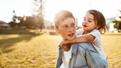 Junge trägt seine kleine Schwester huckepack