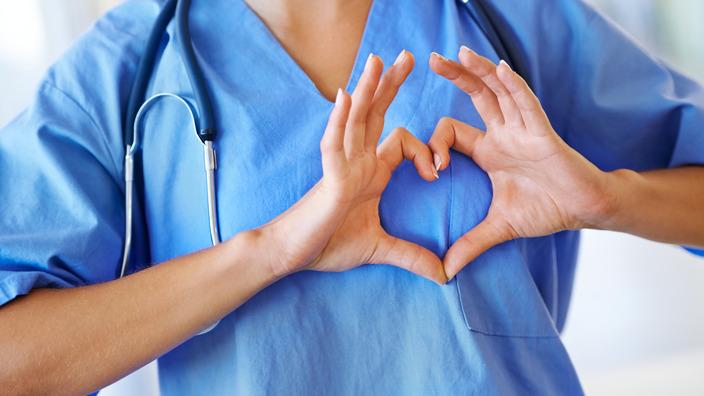 Arzt in OP-Kleidung formt mit seinen Händen ein Herz vor seiner Brust