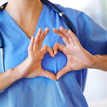 Arzt im OP-Kittel formt mit beiden Händen ein Herz vor seiner Brust