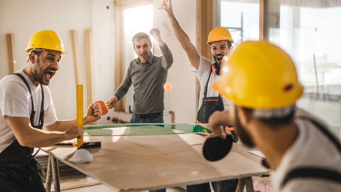 Bauarbeiter spielen Tischtennis auf einer Baustelle