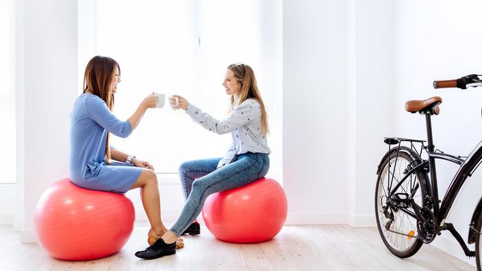 Kolleginnen sitzen während einer Pause auf Gymnastikbällen