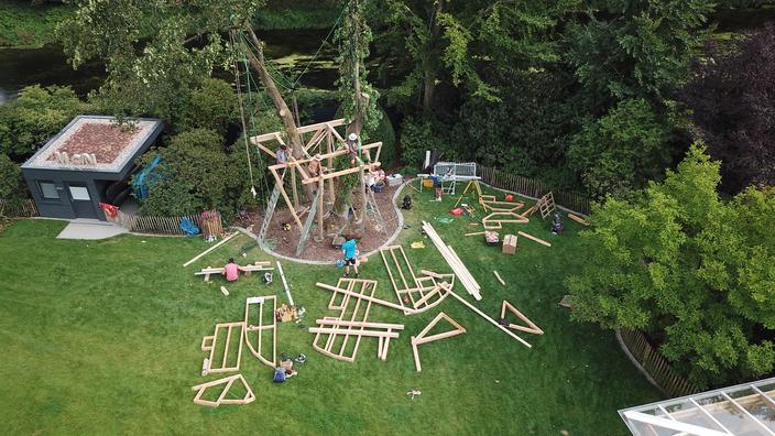 Das Bodengerüst des Baumhauses ist bereits im Baum befestigt, vorgefertige Rahmenteile für Seitenwände und Dachstuhl liegen verteilt auf dem Rasen