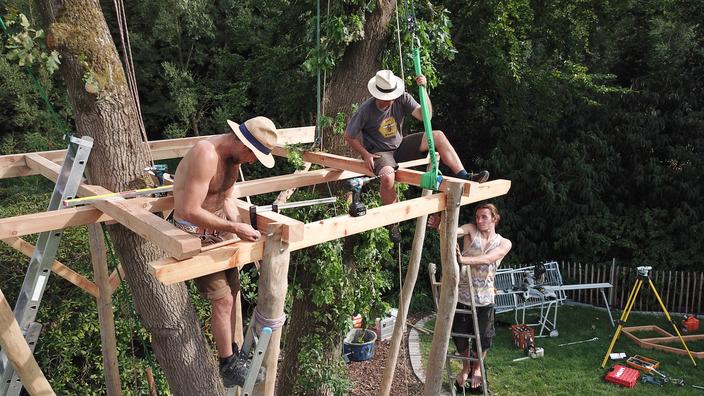 zwei Männer arbeiten am Bodengerüst des Baumhauses