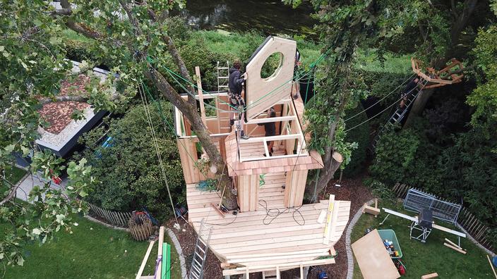 eine Seitenwand mit rundem Fenster wird per Seilzug auf die Baumhausbaustelle gezogen