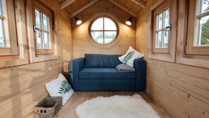 ein blaues Sofa, Kissen und ein Schaffell auf dem Boden machen das Baumhaus gemütlich