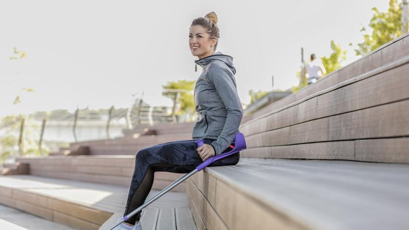 Frau mit Krücke sitzt auf Stufen.