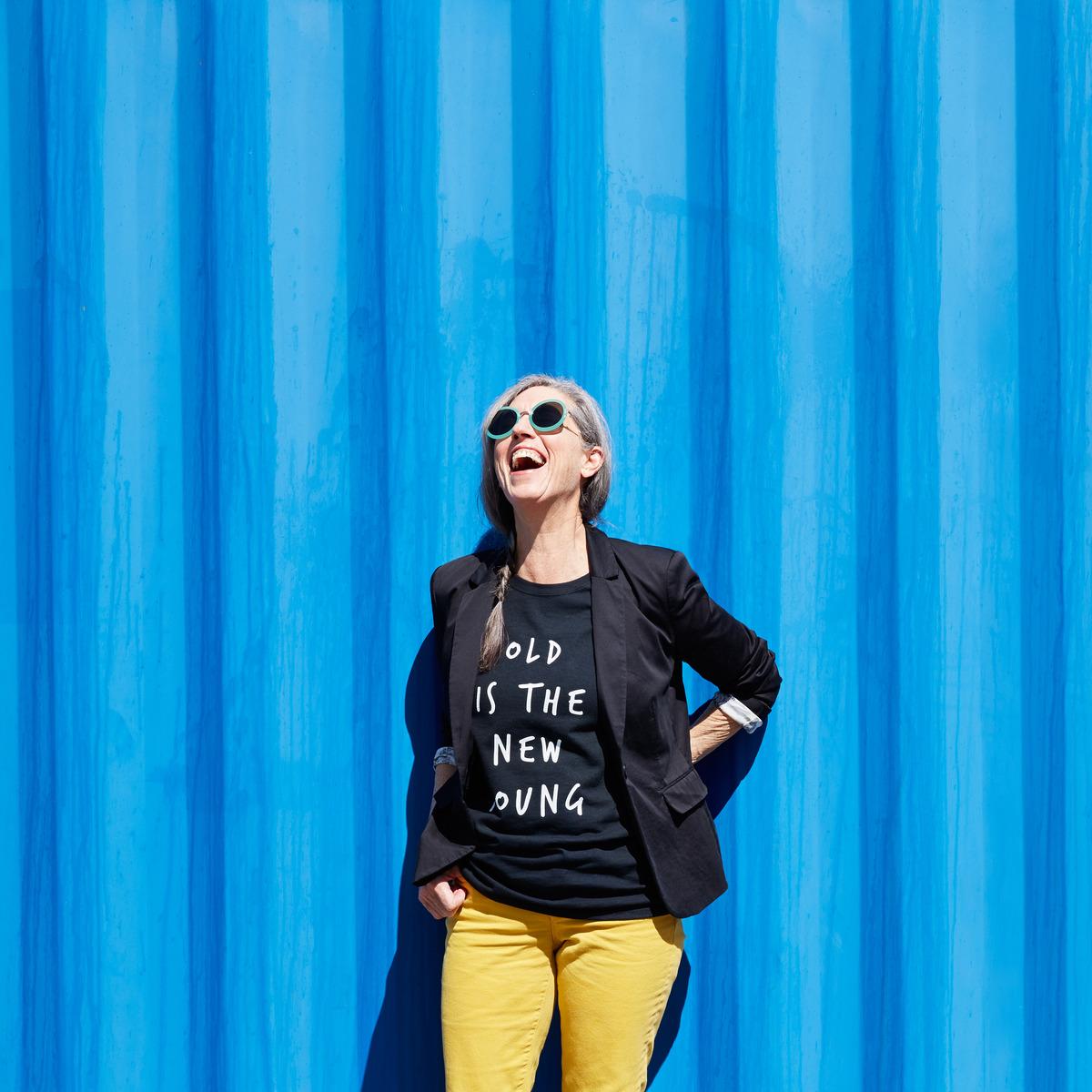 Rentnerin posiert vor blauer Wand