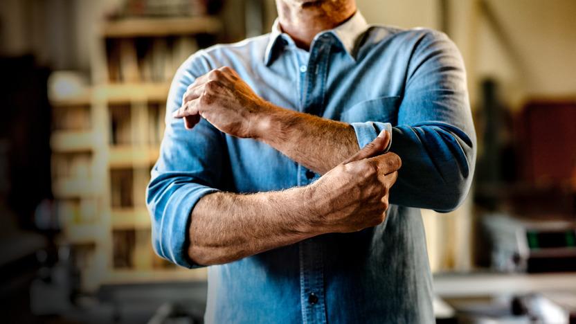 Mann krempelt die Ärmel seines Jeanshemdes hoch