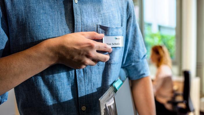 Männlicher Oberkörper im Jeanshemd mit Namensschild an der Brust