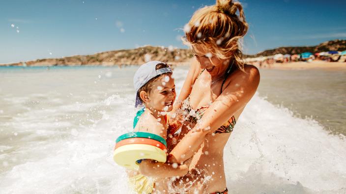 Mutter und Sohn spielen in der Meeresbrandung