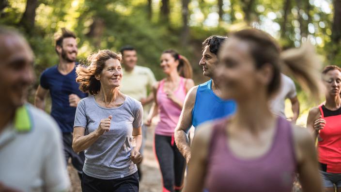Gruppe von Frauen und Männern beim Joggen durch den Wald