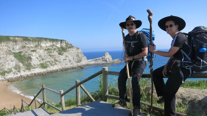 Willi und Ute Lethert sitzen auf dem Geländer einer Treppe, die hinunter zu einem Strand führt.